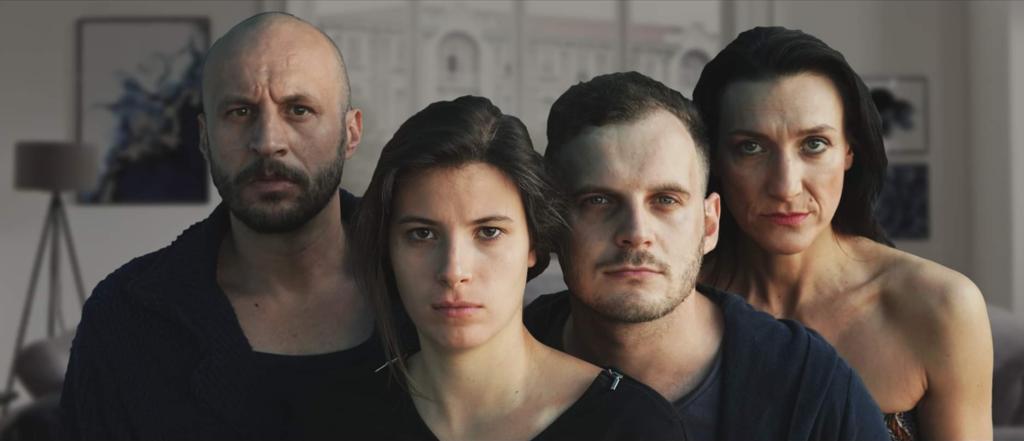 Cztery osoby stoją blisko siebie i spoglądają do obiektywu. Ich twarze są poważne.