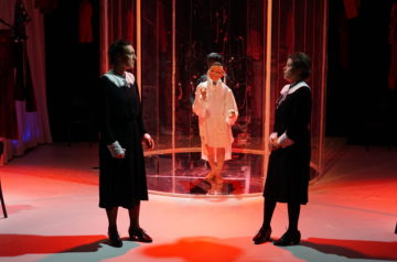 Dwie aktorki w strojach pokojówek stoją na przeciwko siebie. Za nimi aktorka prowadzi lalkę.