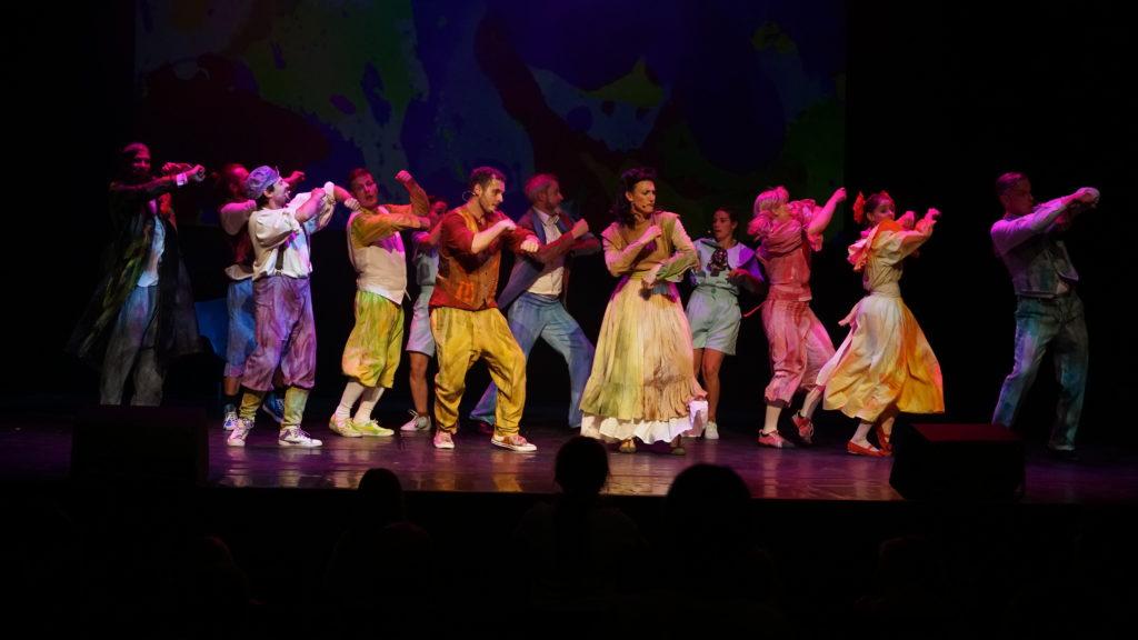 Duża grupa aktorów w kolorowych strojach tańczy na scenie