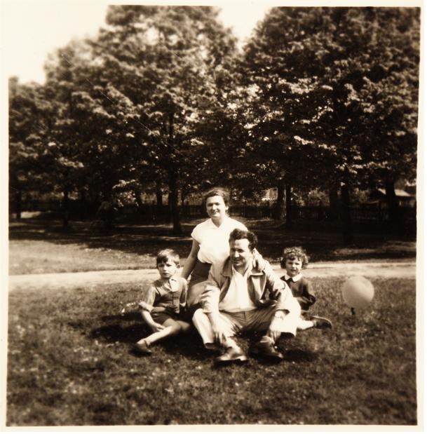 Na trawie nieopodal drzew siedzi Tadeusz Różewicz z żoną i dwójką dzieci.