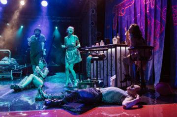 Przy barze siedzi kobieta. Pod jej nogami leży mężczyzna. Obok stoi kobieta i głośno śpiewa.